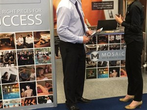 Mosaic's stand with a client visiting